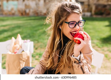 Funny hungry girl with appetite bites off red apple sitting in the park after a shopping trip. Attractive young woman eating turning away on the blur nature background. Lunch in the park, buying food