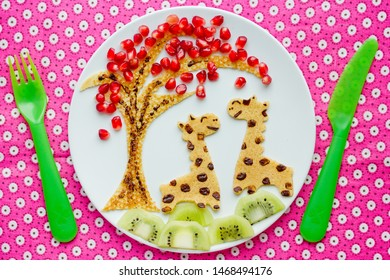 Funny idea for kids breakfast - animal shaped pancake with pomegranate and kiwi slices