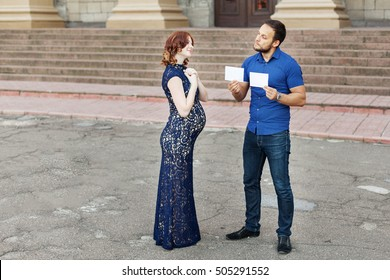 "Funny image. Couple expecting a baby: man holds a signs with space for text ""boy"" or ""girl"". Pregnancy in long dress. Future daddy in jeans and blue shirt."