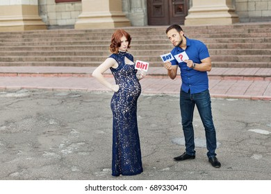 "Funny image. Couple expecting a baby girl: man holds a sign saying ""boy?"" but pregnant mother holds a sign saying ""girl!""  Pregnancy in long dress. Future daddy in jeans and blue shirt."