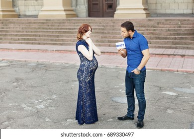 "Funny image. Couple expecting a baby: man holds a sign saying ""boy?"" Pregnancy in long dress. Future daddy in jeans and blue shirt."
