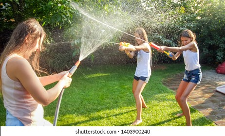 Funny image of happy family with children playing and splashing water with water guns and garden hose at hot sunny day