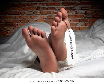 Funny image of a man who is resting covered with a sheet like in the morgue, with a label on his thumb.