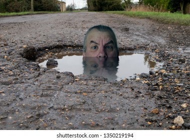 Funny image of mans head in water filled pot hole. concept of how bad roads are.