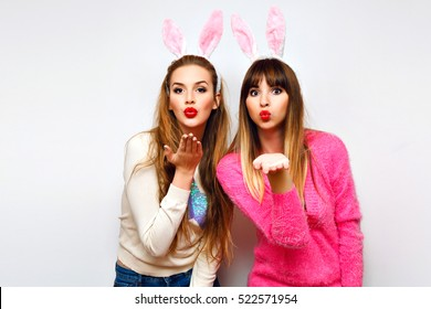 Funny indoor portrait of two happy pretty girls having fun masquerade  party, wearing fluffy bunny ears and bright sweaters, crazy emotions, sending kiss bright colors.