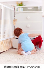 funny infant baby throwing out clothes from the dresser at home