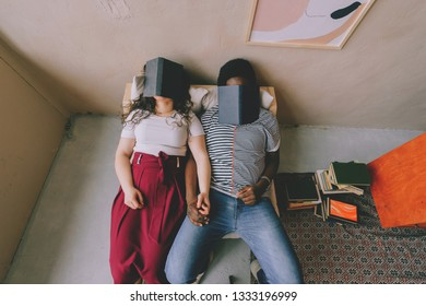 Funny interracial couple sitting in chair in studio and sleeping with books on their faces. Tired dark skinned unrecognizable man fall asleep after reading with caucasian unknown woman at home.