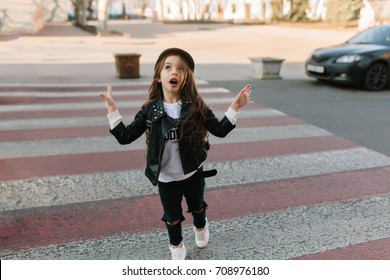 Funny kid with beautiful long hair running to the camera on the crosswalk and looking away. Cute little girl in trendy leather jacket emotionally waving hands while walking down the street.