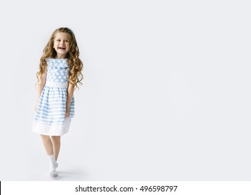 Funny kid in blue and white dress jumping and laughing on light blank background. Little pretty girl isolated on white background. Copy space for text. Sale, holidays, birthday party concept.