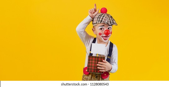 Funny kid boy clown fooling isolated yellow background,studio,blank,copy space for text,design,,advertising. Concept holiday,birthday,day laughter,jokes,1 april,party.Expression child face joy,smile.