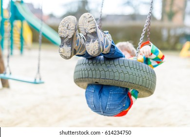 Funny kid boy having fun with chain swing on outdoor playground. child swinging on warm sunny spring or autumn day. Active leisure with kids. Selective focus, no face of kid