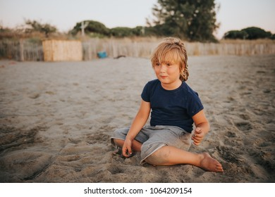 Funny kid boy resting on sand beach by the sea at sunset. Young child enjoying summer vacation on south of France
