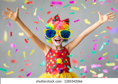 Funny kid clown with pper confetti. Happy child playing at home. 1 April Fool's day concept