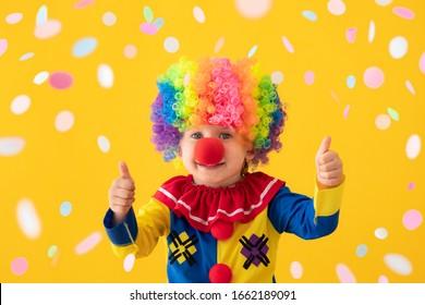 Gracioso payaso que muestra los pulgares hacia el fondo amarillo. Niño feliz jugando interior. 1 de abril Concepto del Día de los Inocentes