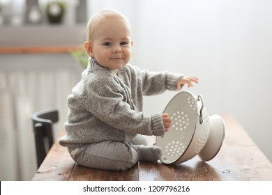 Funny Kid in a comfortable sweater playing in a cozy real kitchen, lifestyle and light smoky toning