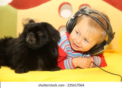 funny kid with a dog listening to music in headphones