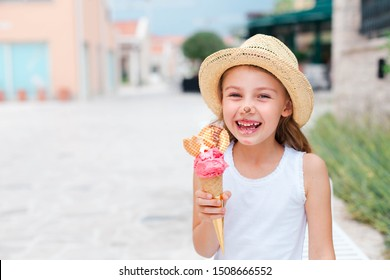 Funny kid is eating ice cream. Child is enjoying melting italian gelato. Happy cute girl in straw hat is laughing and tasting delicious street food in summer vacation. Lifestyle moments of childhood.