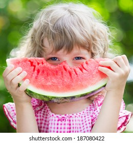 Funny kid eating watermelon outdoors in summer park. Child, baby, healthy food