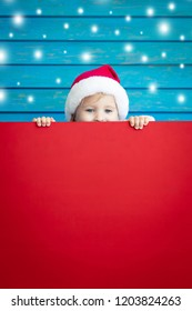 Funny kid holding cardboard banner blank. Child playing at home. Christmas holiday concept. Copy space.