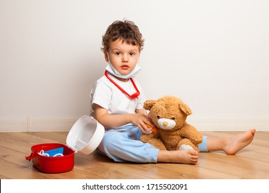 funny kid in a medical mask plays with a teddy bear at the doctor. A child in a mask measures pressure and listens to a toy with a stethoscope. virus protection training
