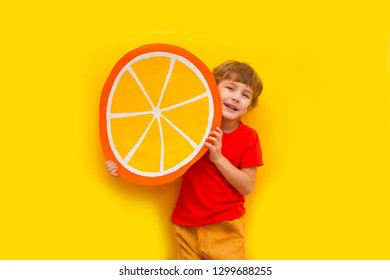 Funny kid with orange from a cardboard on a yellow background. healthy food. Concept summer lifestyle.