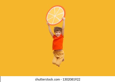 Funny kid with an orange segment from a cardboard jump on a yellow background. healthy food. Concept summer lifestyle.