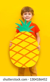 Funny kid with pineapple from a cardboard on a yellow background. healthy food. Concept summer lifestyle.