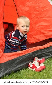 funny kid playing in a tent on the nature