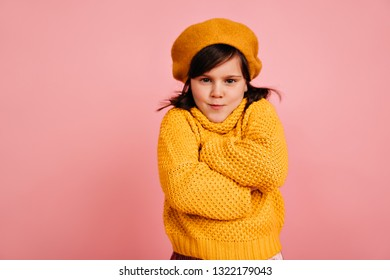 Funny kid posing with arms folded. Studio shot of preteen girl wears yellow clothes.