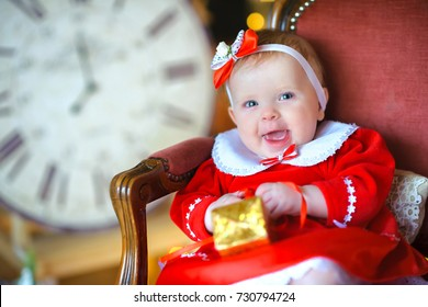funny kid sits in an armchair in a gift in his hands, expectation of a holiday