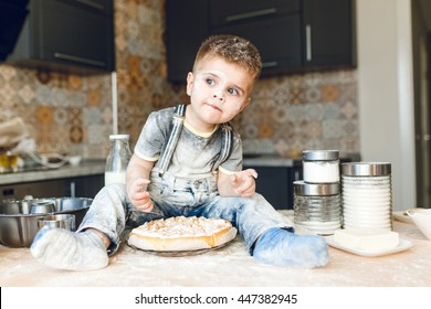 Funny kid sitting on the kitchen table in a rustic kitchen playing with flour and tasting a cake. He is covered in flour and looks funny. He looks curious. Milk and different jars stand on the table.