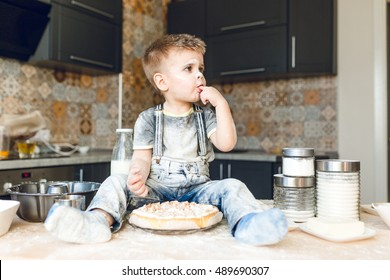 Funny kid sitting on the kitchen table in a rustic kitchen playing with flour and tasting a cake. He is covered in flour and looks funny. He puts his finger in the mouth.