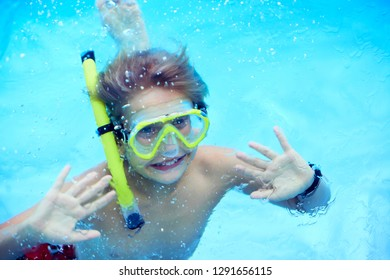 Funny kid in snorkeling mask diving under water