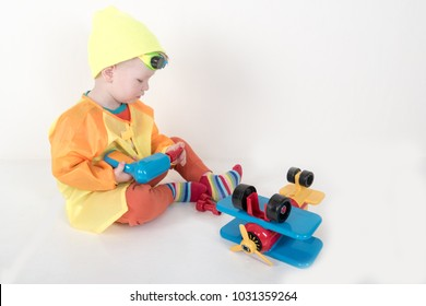 Funny kid in sunglasses and a bright ski suit. A child plays with a toy airplane representing himself as a pilot.
