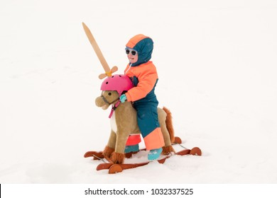 Funny kid in sunglasses and a bright ski suit. A child plays with a wooden sword sitting on a toy horse, presents himself as a superhero. Winter village vacation  on ice-covered river with snow.