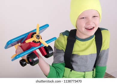 Funny kid in sunglasses with glasses and a bright ski suit. A child plays with a toy airplane representing himself as a pilot. The boy is happy spending vacations in the village. Winter Joys and Snow