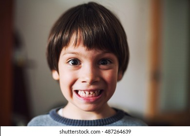 Funny kid with surprised face in a room