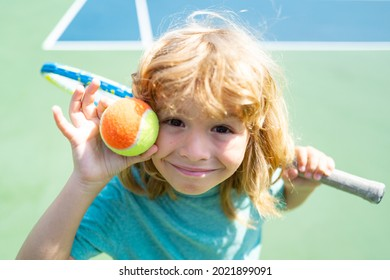 Funny kid tennis player on tennis court. Funny kids face.