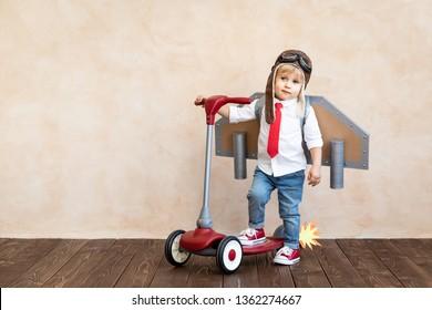 Funny kid with toy jet pack. Happy child playing at home. Success, imagination and innovation technology concept