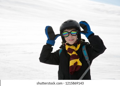 Funny kid with in warm clothes and protection equipment taunts. White snow background.