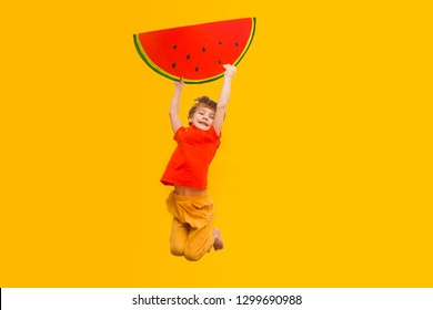 Funny kid with watermelon from a cardboard jump on a yellow background. healthy food. Concept summer lifestyle.
