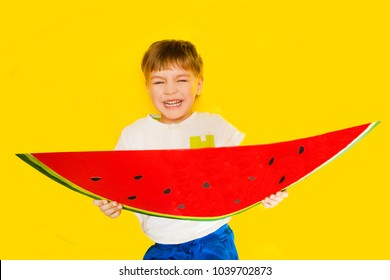 Funny kid with watermelon from a cardboard on a yellow background. healthy food.
