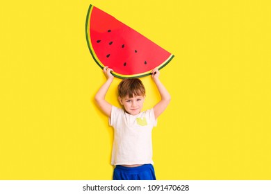Funny kid with watermelon from a cardboard on a yellow background. healthy food. Concept summer lifestyle.