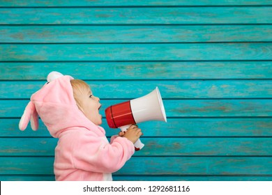 Funny kid wearing Easter bunny. Child speaking by megaphone. Spring holidays concept