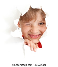 funny kid with wink eye portrait in torn paper hole isolated