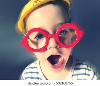 funny kid with work helmet and red glasses and blurred background