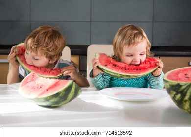 Funny kids eating watermelon in kitchen of the house. Healthy Eating