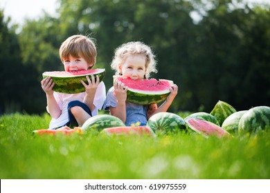 Funny kids eating watermelon outdoor. Summer healthy food.