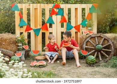Funny kids eating watermelon outdoors in the garden. Children having picnic outdoors in summer park. Happy boys eating watermelon. Healthy eating, snack for children. Childhood. Summer time. Friends