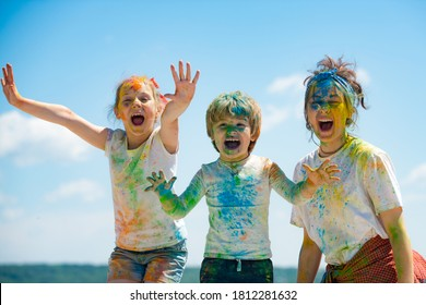 Funny kids face in color splash, coloured powder on children body. Cheerful friends showing hands painted in bright colors. Colorful dirty people